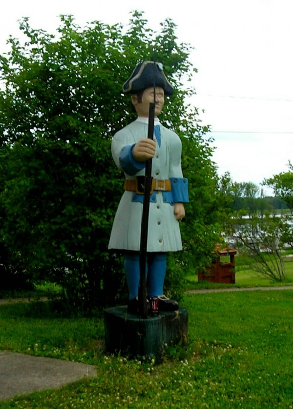 Wooden statue on the Oromocto waterfront, highlighting the town's military heritage.