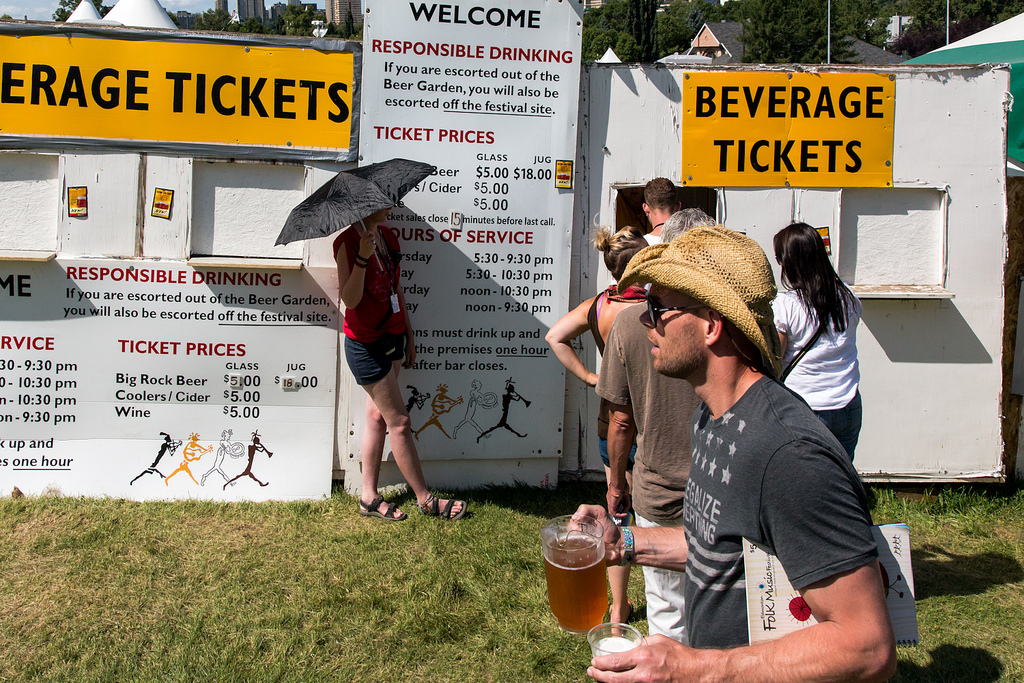 Festival-goers line up for drinks in the beer garden at the Edmonton Folk Music Festival. Folk Fest has been a magnet for music lovers every August at Gallagher Hill since 1980. © Tom Young 2012
