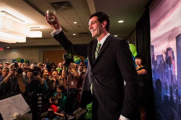 """A quick glass of """"Edmonton's finest"""" mid-speech while his wife Sarah looks on."""