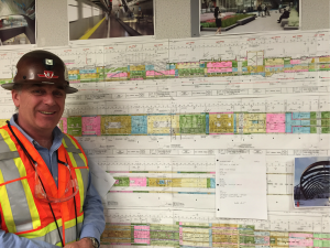 Dragomir Jevremovic, Construction Site Manager, Vaughan Metropolitan Centre Station stands with construction drawings. The colour coding indicates construction progress.