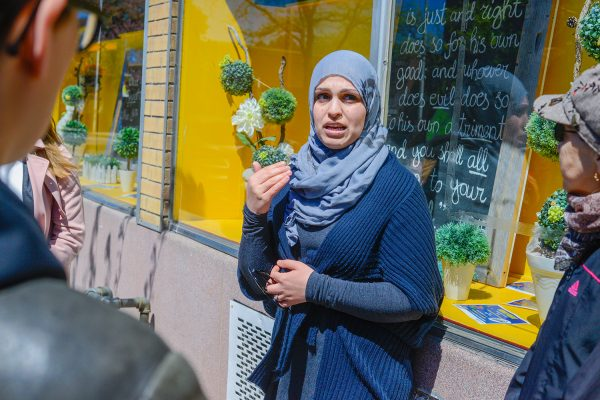 Community organizer Rusul Alrubail stands in front of the Toronto Dawah Centre's storefront display to share her story about the White Ribbon Campaign.