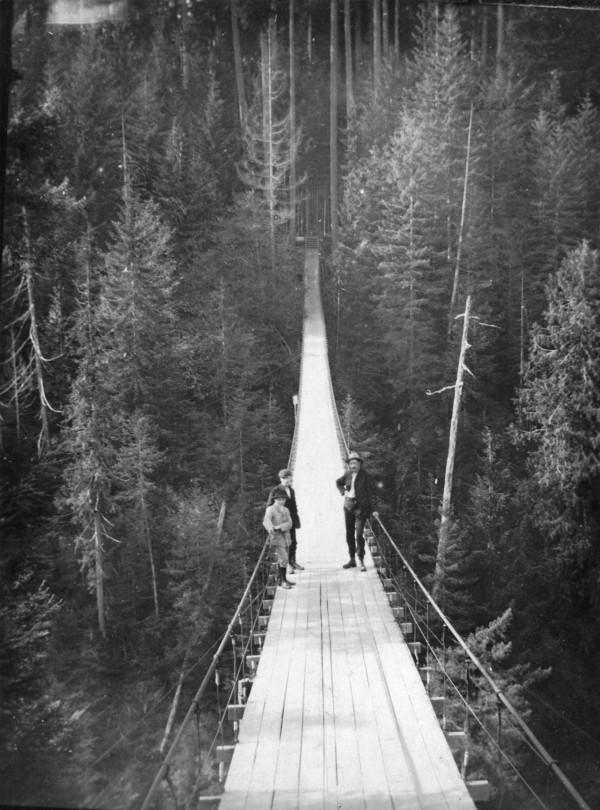 CVA 677-62 Three people crossing the Capilano Suspension Bridge, 1910.