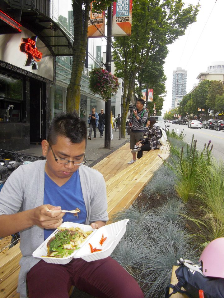 The decking, vegetation, and wooden bench of Urban Pasture parklet adds a semi permanent extension of pedestrian space on Robson to socialize and eat. [Photo: John Paul Catungal]